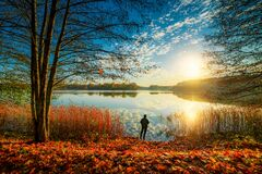 fishing in fall sunrise, forest lake and beautiful scenic fall nature