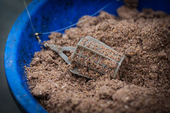 Fishing feeder lure in mixed groundbait. Royalty Free Stock Photos