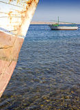 Fishing felluca on it's mooring. Small fishing boat anchored off the beach Stock Photo