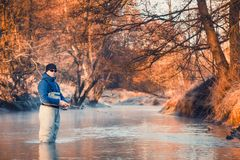 Fishing. Fisherman with casting rod standing in river. Fisherman angling trout. Fisherman in waders. Autumn landscape. Leisure activity royalty free stock photos