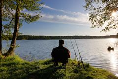 Fishing. Fisherman sitting on the chair and fishing on the shore of lake during sany day Royalty Free Stock Photos