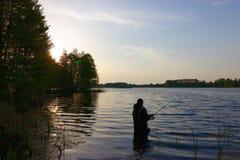 Fishing. Fisherman standing in lake with fishing rod Stock Photos