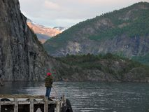 Fishing in a fjord. Man fishing from a pier in a fjord Stock Photography