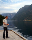 Fishing in the fjord. Young man fishing in a Norwegian fjord Royalty Free Stock Images