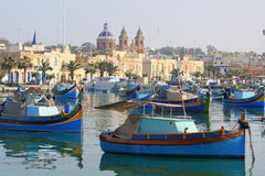 Fishing vessels at anchor. Traditional fishing vessels also known as luzzus and kajjiks at anchor in the fishing port of Marsaxlokk in Malta Stock Image