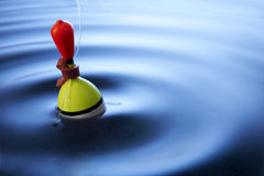 Fishing Float. Multi coloured fishing float bobbing in water making ripples royalty free stock images