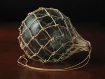 Fishing Float. An old blue glass fishing float in a knotted string net stock photos