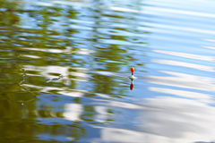 Fishing float on water with waves and beautiful reflection Royalty Free Stock Images
