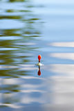 Fishing float on water with waves and beautiful reflection Royalty Free Stock Photo
