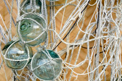 Fishing floats. Vintage glass fishing floats with fishing nets against a woven background Stock Photography