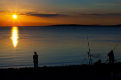 Fishing for flounder at sunset on the seashore royalty free stock photo