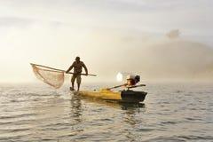 Fishing on the foggy lake Stock Photography