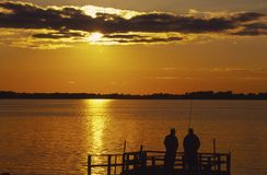 Fishing Friends. Two friends fishing in the light of sunset Royalty Free Stock Photography