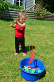 Fishing Game. Adorable little girl is playing fishing game in the home garden Royalty Free Stock Photography