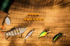 Fishing gear, artificial bait on a predator on a wooden background, top view with inscription love fishing wobblers and Royalty Free Stock Photos