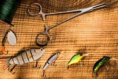 Fishing gear, artificial bait on a predator on a wooden background, top view wobblers and various bait cords and tongs. On a wooden background Royalty Free Stock Photos