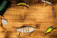Fishing gear, artificial bait on a predator on a wooden background, top view wobblers and various bait cords and tongs. On a wooden background place for Stock Images