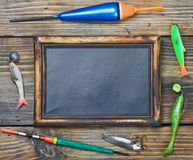 Fishing gear and blackboard. On wooden background Royalty Free Stock Images