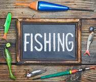 Fishing gear and blackboard. On wooden background Stock Image