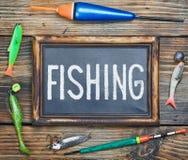 Fishing gear and blackboard Stock Image