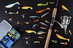 Fishing gear on a dark table. Spoon-baits, wobblers, multicolored bait for fish on the table. Stock Photos