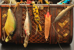 Catch the Big Fish with the Best Lure. Colorful fishing lures hanging from a weaved brown basket, close-up Royalty Free Stock Images
