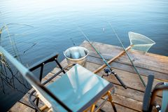 Fishing gear on the pier on the lake. Place for fishing with fishing rods, net and bucket on the wooden pier on the lake stock images