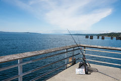 Fishing Gear on Pier. Recreational fishing gear - rods and reels, tackle box, net, lures, hooks - on pier. Copy space stock photo