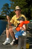 Fishing with Grandpa. Young boy fishes with his grandpa. He has caught a bream and is admiring his catch. Child has on denim overalls and black rubber boots royalty free stock photo