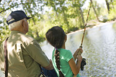 Fishing with Grandpa. A young girls fishing with her grandpa on a warm summer day stock photo
