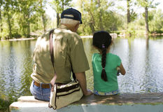 Fishing with Grandpa. A young girls fishing with her grandpa on a warm summer day stock photos