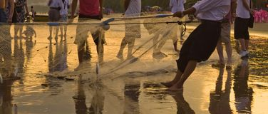 Fishing with group of Hainan fishers gathering the net. Image of sunset fishing with group of Hainan fishers gathering the net on the beach and casual observers Royalty Free Stock Images
