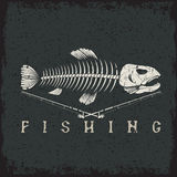 Fishing grunge emblem with skeleton of trout Royalty Free Stock Photos