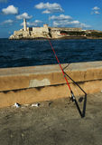 Fishing on Habana malecon. A fishing rod standing over malecon wall with The Morro fortress in Havana bay on the background Royalty Free Stock Photo