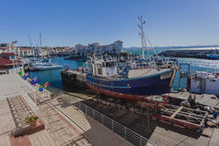 Fishing Harbor Cape St.Francis. Fishing boat up skip way dry and other boats moored with home around the fishing port at Cape St.Francis South-Africa Royalty Free Stock Photo