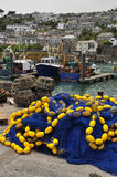 Fishing harbour of Newlyn. Cornwall, England, UK. The fishing harbor of Newlyn, Cornwall, England, Britain. Fishing boats, nets and village view Stock Images