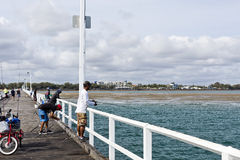 Fishing in Harvey Bay. People enjoying recreational fishing from the pier in Harvey Bay, Australia Stock Photos