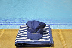 Fishing hat and striped towel in the pool Stock Photos