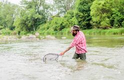 Fishing hobby. Bearded brutal fisher catching trout fish with net. If fish regularly you know how rewarding and soothing