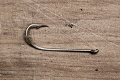 Fishing hook. Fishing hook on wooden table, close up Stock Photos