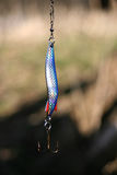 Fishing hook. A colorful fishing hook in blue and silver royalty free stock images