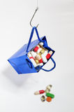Fishing hook holding a blue bag with medicines Stock Photos