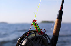 Fishing hooks and reel close-up. Close-up shot of fly fishing rod with equipment Stock Image