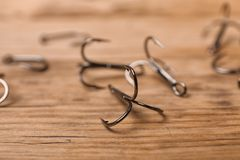 Fishing hooks on wooden table. Angling equipment royalty free stock photos