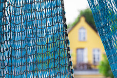 Fishing House. Blue fishing net and an old beautiful yellow house at the background stock photography
