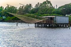 Fishing house in Comacchio, delta del Po. Fishing house in Comacchio, delta of Po river, in Emilia Romagna, Italy; there are nets in front of the fishing house royalty free stock photography
