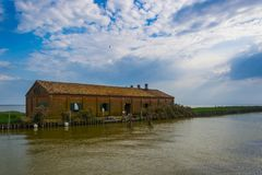 Fishing house on the delta Po river. Typical old fishing house on an island in the delta of Po river, used for fishing eels, near Comacchio a small town in stock photos