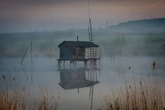 Fishing house on the water in the morning fog.  stock images