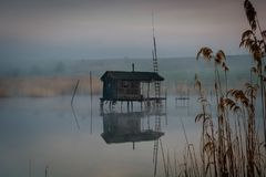 Fishing house on the water in the morning fog.  stock photos