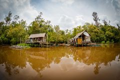 Fishing houses in Borneo. Typical dwelling indigenous fishermen on Borneo rivers Stock Images